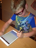 Boy writing on ipad